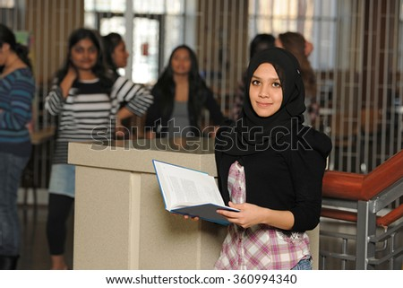 Young Muslim college student with diverse people inside building - stock photo
