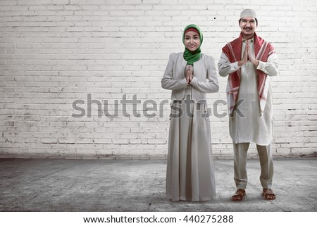 Young muslim couple smiling with white brick wall background