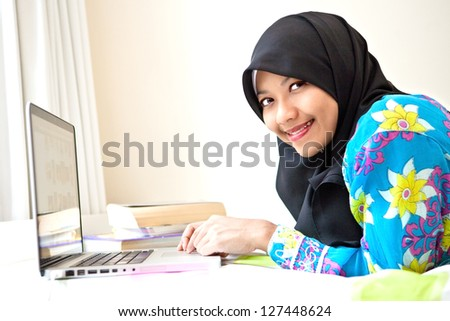Young Muslim female student with laptop - stock photo