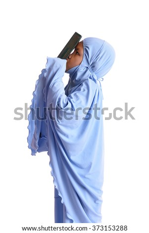 Young Muslim Girl in Love with Holy Book of Quran Isolated on White Background - stock photo