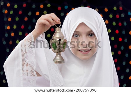 Young Muslim Girl in White Hejab Holding Ramadan Lantern on Defocused Night Lights Background - stock photo