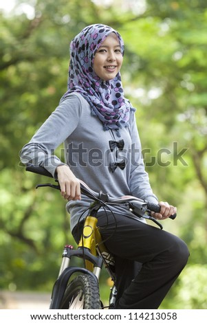 Young Muslim girl on bicycle