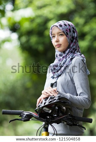 Young Muslim girl on bicycle waiting in the park