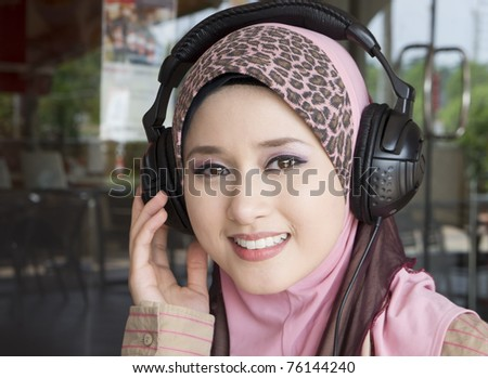 young muslim girl smile with headphones - stock photo