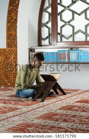 Young Muslim Guy Reading The Koran - stock photo