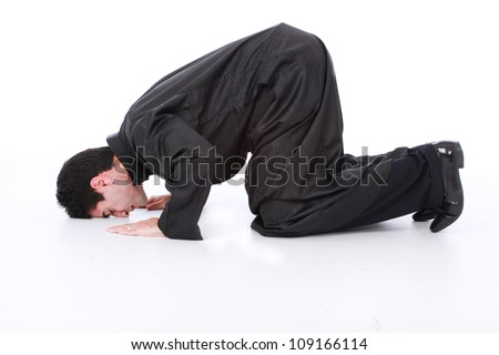 Young Muslim man wearing traditional clothing praying and practicing the Islamic faith on a white isolated seamless background