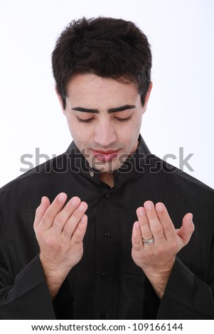 Young Muslim man wearing traditional clothing praying and practicing the Islamic faith on a white isolated seamless background - stock photo