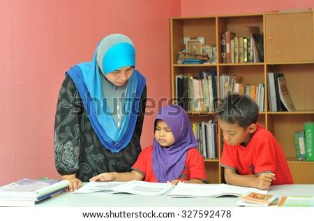 Young Muslim mother teaching her kids doing homework - stock photo
