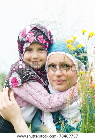 Young muslim mother with daughte in a grass