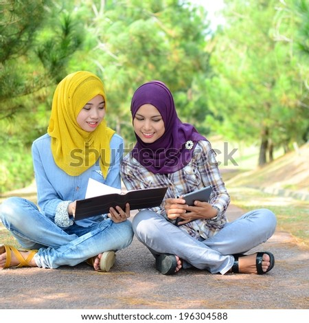 Young Muslim students smiling and happy with a mobile laptop. - stock photo