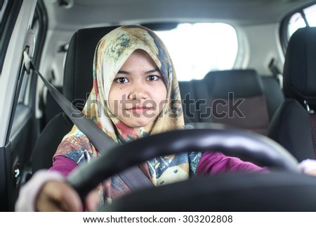 young muslim woman driving her car - stock photo