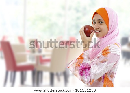 Young Muslim woman eating apple, healthy eating concept - stock photo