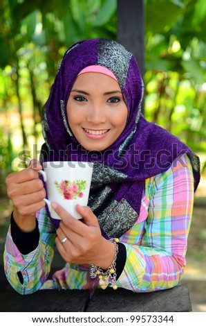 young muslim woman in head scarf holding a cup of tea and smiling
