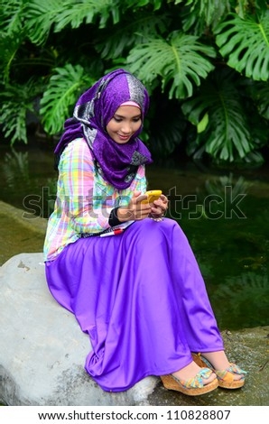 young muslim woman in head scarf using phone