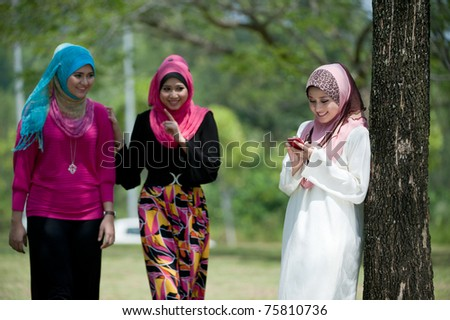 young muslim woman in head scarf using phone in the park