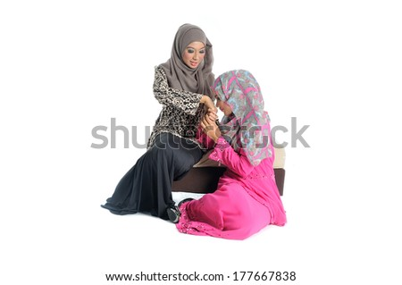 young Muslim woman in head scarf with modern clothes asking forgiveness from elder sister,  isolated on white - stock photo