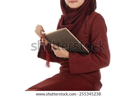 Young muslim woman read Quran with tasbih in the Ramadan time, on a chair - stock photo