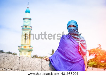 Young muslim woman standing with traditional islamic clothing - Portrait of asian girl with veiled face on minarets background - Concept of world religions - Soft vintage filter with sunset lights - stock photo
