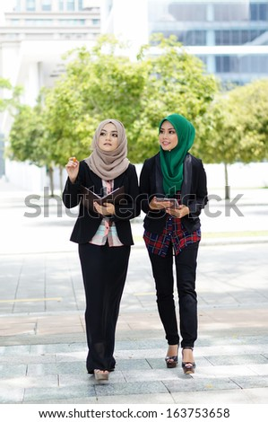 young muslimah discussing while walking at park - stock photo