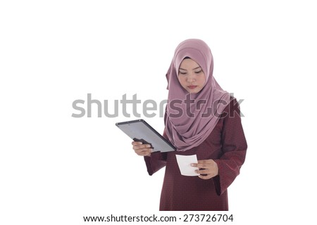 Young muslimah woman reading receipt. - stock photo