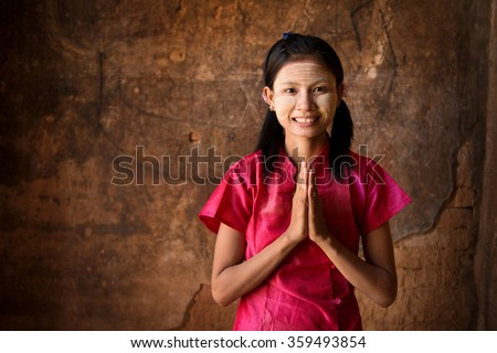 Young Myanmar woman in a traditional welcoming gesture.