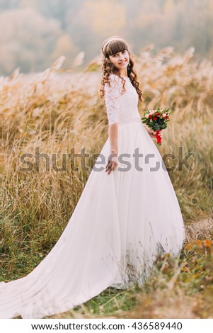 Young naive bride posing outdoors. Cute charming girl with forest hills on background - stock photo