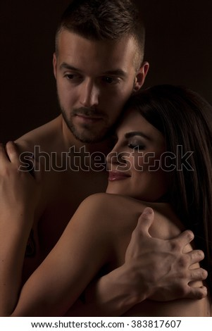 young naked couple in an embrace on black background