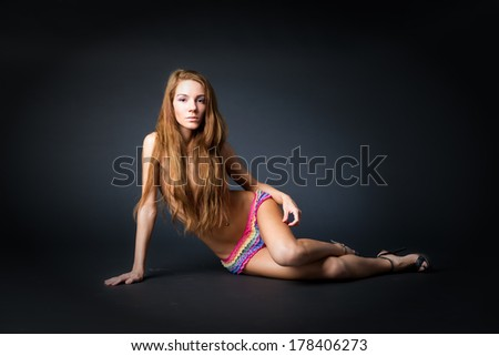 Young naked girl in studio. Beautiful woman with long hair