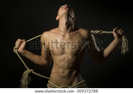 Young naked handsome man with sexy strong muscular body with long durable rope standing on studio black background, horizontal picture - stock photo