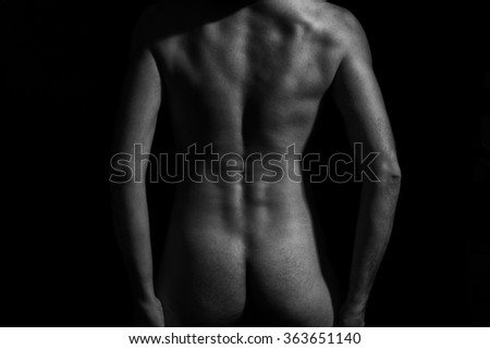 Young naked man on a black background
