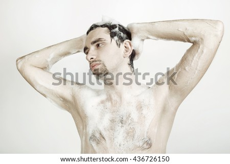 Young naked man taking shower in the foam - stock photo