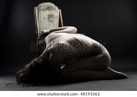 Young naked woman curling up on the floor in grief