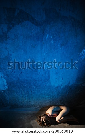 Young naked woman lying down on the floor. Hiding her face. Sexual parts are not visible. Rape or violence victim concept. - stock photo