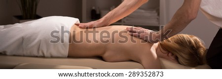 Young naked woman lying on couch during spinal column massage