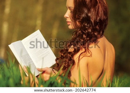 Young naked woman reading book at summer field. - stock photo