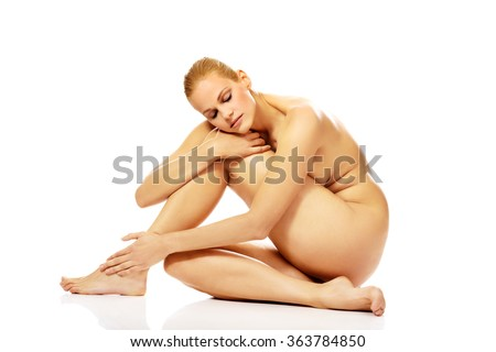 Young naked woman sitting on the floor and touching her leg