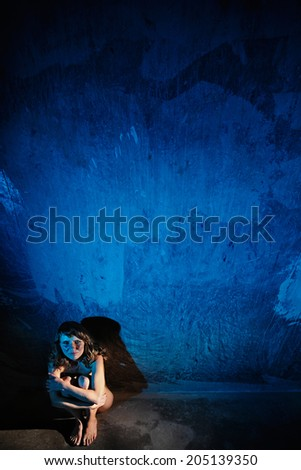 Young naked woman sitting on the floor crying looking at camera. Sexual parts are not visible. Rape or violence victim concept. - stock photo
