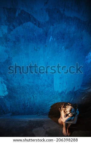 Young naked woman sitting on the floor. Hiding her face. Sexual parts are not visible. Rape or violence victim concept. - stock photo