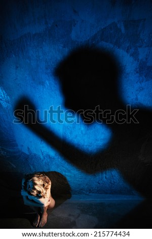 Young naked woman sitting on the floor. Hiding her face. Sexual parts are not visible. Shadow of man hitting woman with fist on the wall. Rape or violence victim concept. - stock photo