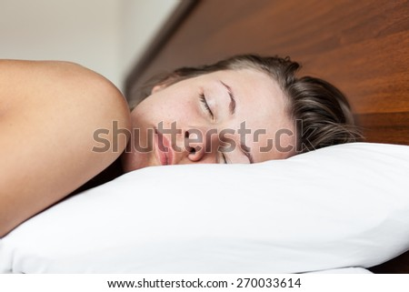 Young naked woman sleeping in white bed in the morning