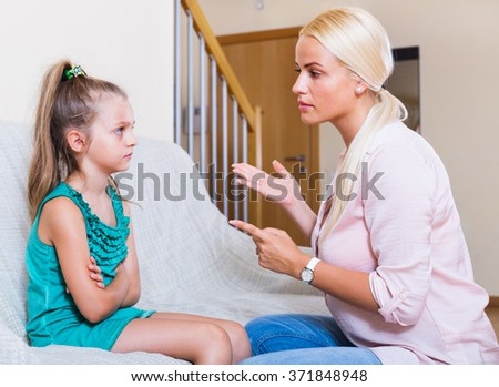 Young nanny scolding at little girl at a home interior