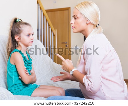 Young nanny scolding at little girl at home interior