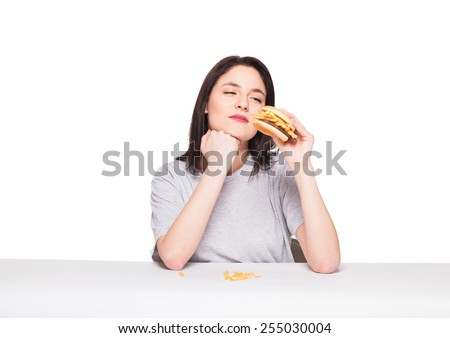 young natural woman eating junk food, hamburger and fries, on white background - stock photo