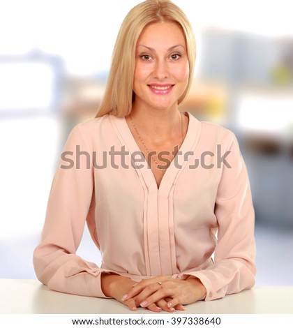 Young natural woman with clean face sitting at white table leaning on her elbows, over white background - stock photo