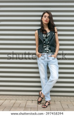 Young naughty fashionable brunette woman in black leather jacket posing outdoors against urban style background of metal strips - stock photo