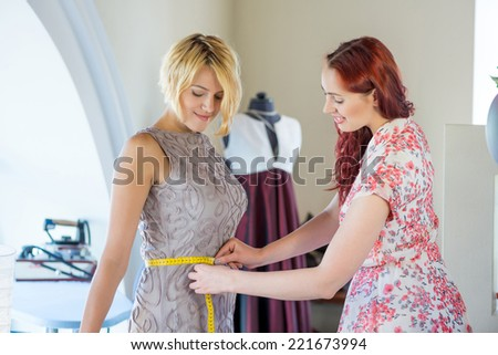 Young needlewoman taking measures of female client - stock photo