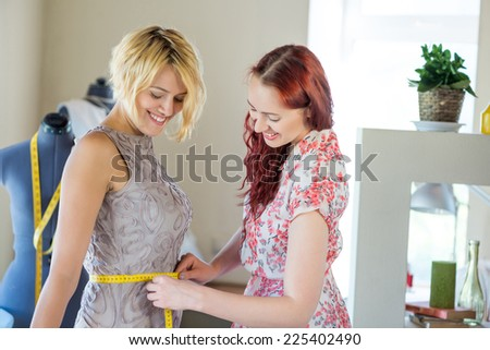 Young needlewoman taking measures of female client