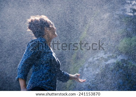 Young Nepalese woman standing in the water spray from a waterfall - stock photo