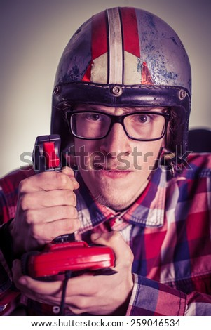 Young nerd playing video games on retro joystick - stock photo
