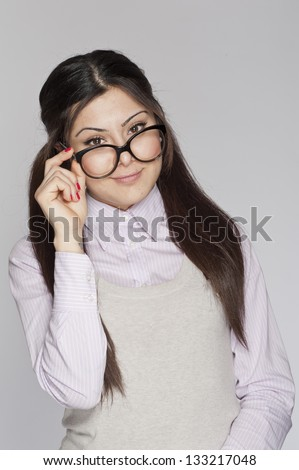 Young nerd woman playing with her glasses - stock photo